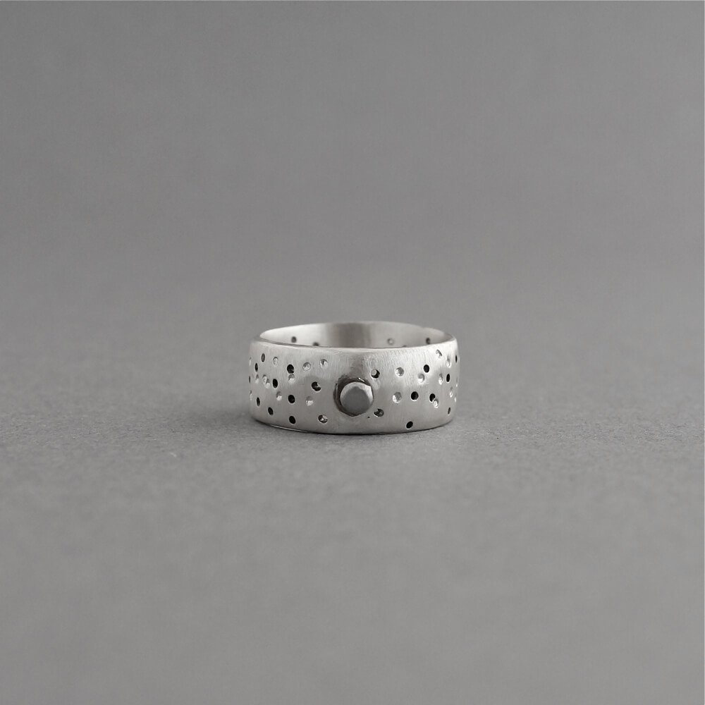Melanie Decourcey/silver ring with holes & dotes & round center