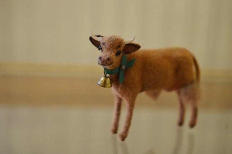 カウベルを付けた小さな角の生えた茶色の牛